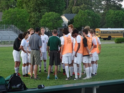 BOYS VARSITY SOCCER circles up for a team talk before the game.