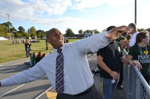 COACH ROBERT JAMISON throws out a t-shirt to the crowd of students awaiting the homecoming pep rally.