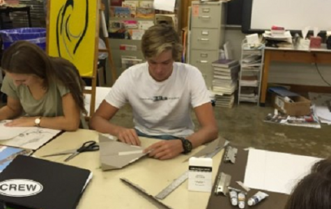 SENIOR JACK SULLIVAN makes a paper airplane for an Art class project.