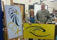 ADVANCED ART TEACHER Cathy Opfer presented local Army Recruiters student-painted ceiling tiles representing the school.