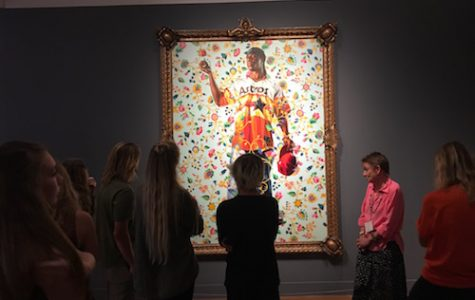 STUDENTS OBSERVE A painting while a curator gives insight on it.
