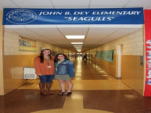 SENIOR TARA LARUSSO and junior Taylor Schoolar in front of John B. Dey sign.