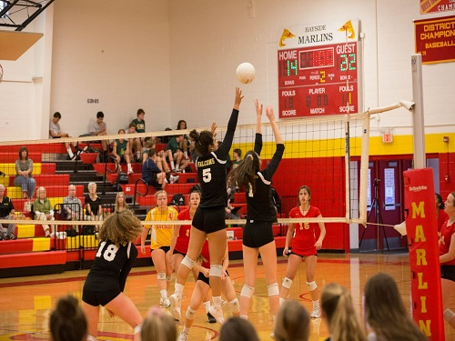 SENIORS MADDIE BUTKOVICH and Rachael Humphrey block a hit from Baysides outside hitter ending in a win against the Marlins.