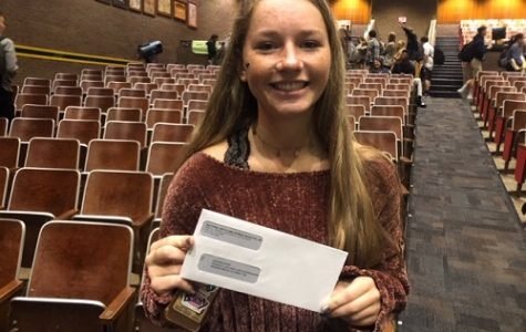 JUNIOR JORDAN ESTES holds her check for scoring well on lone her AP exams last year.  NMSI awarded approximately 50 students these checks yesterday at a ceremony in the auditorium.