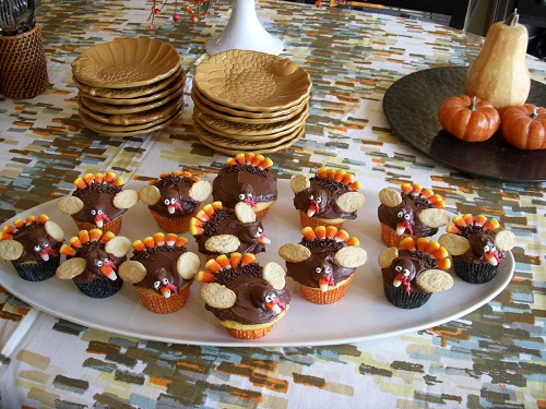 TURKEY DECORATED CUPCAKES sit on a platter, ready to be eaten. Many kids and families create cupcakes with decorative turkey designs for Thanksgiving.