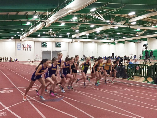 THE GIRLS INDOOR track team members take off on the start line in an indoor arena.  The team had four meets this year and hopes to send some of it's members to post season meets.