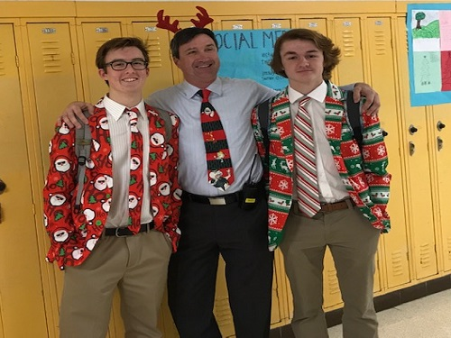 PRINCIPAL DR. KELLY (middle) and a sophomore Santa duo show their holiday spirit with their eccentric Christmas attire.  Each spirit day has a different theme and students are always encouraged to participate in the festivities.