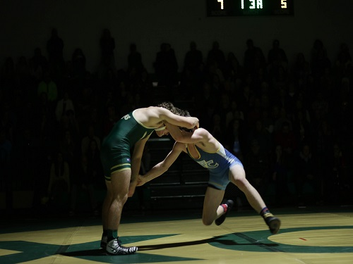 A COX WRESTLER lunges forward at his opponent from First Colonial High School. The wresting team defeated the patriots by a score of 48-27.