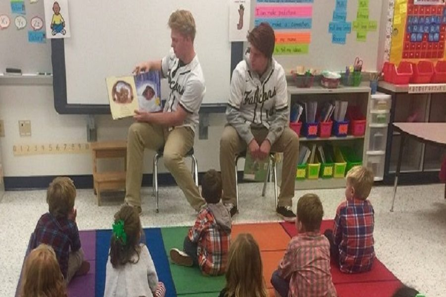 SENIOR BASEBALL PLAYER Spencer Lambert and freshman Ethan Anderson take turns reading to a classroom of elementary school students at Trantwood Elementary.  The baseball players joined the field hockey team at John B. Dey Elementary to read the same book to a new audience.