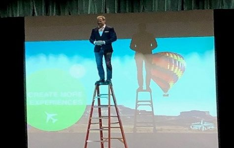 FORMER DENVER BRONCO skydiver Kenyon Salo stands on top of a ladder to encourage students to step out of their comfort zones. Salo was invited by Operation Smile to speak about spreading love and giving back to the community.