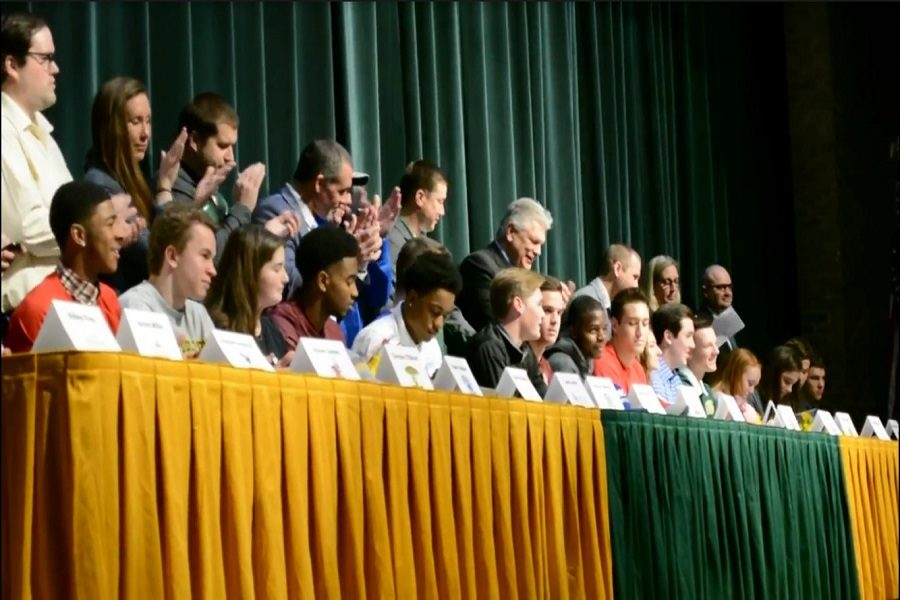 VARIOUS STUDENT-ATHLETES gather in the auditorium to sign to their [respective] colleges for their chosen sport next fall. Parents, teachers, coaches, friends, and family were invited to join in the festivities.