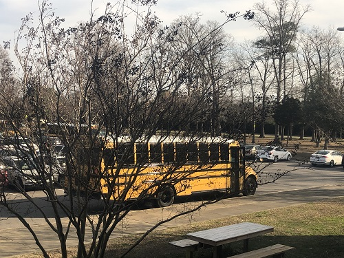 A SCHOOL BUS waits to pick up students outside of school at the 2:10 dismissal. The new Here Comes the Bus app now allows parents to track when their students buses and when it will arrive at their bus stops.