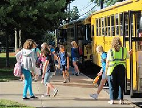Children get off the bus and prepare to walk into school. Here Comes the Bus has allowed parents to track when these busses arrive.