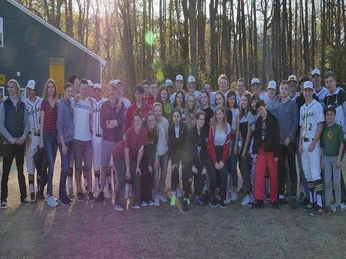 GERMAN+EXCHANGE+STUDENTS+pose+with+the+school%27s+baseball+team+after+their+game+on+Wednesday+Apr.+3.+The+students+helped+cheer+on+the+baseball+team+to+victory.+