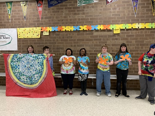 STUDENTS FROM THE Special Education department pose with puzzle pieces. Students then sold the puzzle pieces and other items to raise money during Autism Awareness Month.