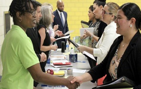 INTERESTED CITIZENS TALK to VBCPS representatives at the Career Expo. The representatives gave out information regarding employment opportunities in Virginia Beach City Public Schools.