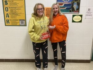 SENIORS SYDNEY AND Laine Hillier model their creative DIY Halloween costumes. Packs of Smarties candy were  taped to regular pants, transforming them into an ironic ensemble.