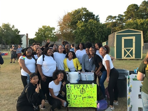 THE STEP TEAM sells pizza at the bonfire before they perform their annual step. Step members choose this venue to fund raise and perform simultaneously as both are for a good cause.