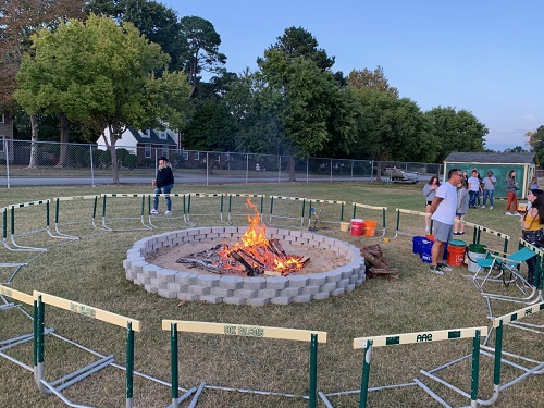 STUDENTS AND TEACHERS build a bonfire that will be used to initiate the Homecoming week festivities on Monday.  Teacher Mr. Kwiatkowski is monitoring the bonfire itself, while talking to students outside its perimeter.