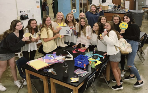 OPERATION SMILE MEMBERS decorate Mrs. Clark's door as part of the Homecoming week celebration. They used the opportunity to spread the word about Operation Smile and all the club does to support those in need.
