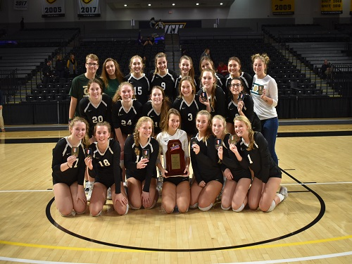 THE GIRLS VOLLEYBALL team surrounds their newly won state championship trophy. The team won a long string of major games to make it to that point.
