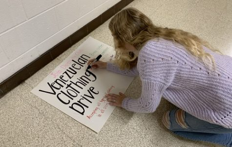 SENIOR AUDRA CHAFFINCH puts finishing touches on a poster for the Venezuelan Clothing Drive. The drive hosted by the Diversity Club will prompt student involvement and community engagement during the holiday season.