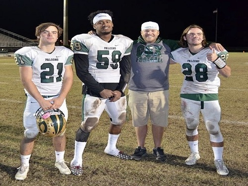 ALUMNUS, MENTOR AND former athlete, football coach Tyler Noe (middle right) enjoys the win with former players after beating rival First Colonial High School. Noe has been a pivotal member of the coaching staff as well as a mentor to the athletes.
