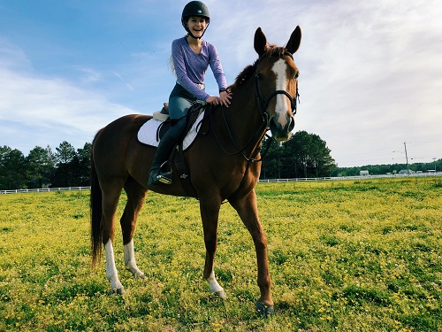 SENIOR AUDRA CHAFFINCH rides her horse, Rue, in the field during an ordinary outing.  She is training Rue for local competitions with hopes of reaching the national level.