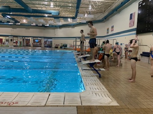 RELAY TEAM SWIMMERS prepare to dive into water. The Falcons gained most of their points from the relay wins.