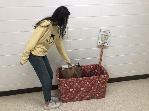 SENIOR ALEX PEREZ drops off a toy in one of the Noble Teens donation boxes, this one located outside of Mr. Horowitzs room. The goal is to fill each of these boxes to the brim by Thursday, Dec. 19, to  have enough toys to donate to children in need.