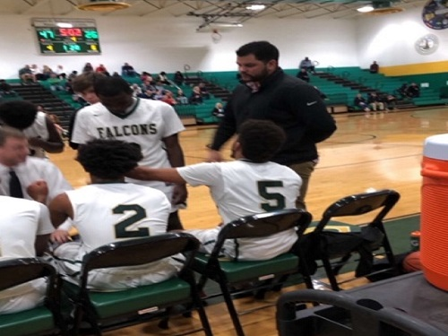 VARSITY BOYS BASKETBALL players huddle up during a time-out in the season opener against Kellam High School. The Falcons were getting pumped up by a pep talk from Head Coach Bobby Wolfe.