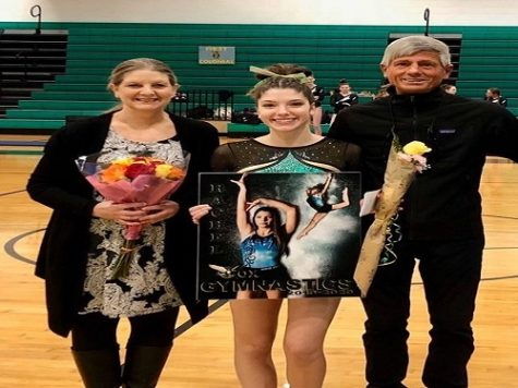 SENIOR RACHEL RUHL celebrates senior night with her parents. She has been on the gymnastics team since her freshman year.