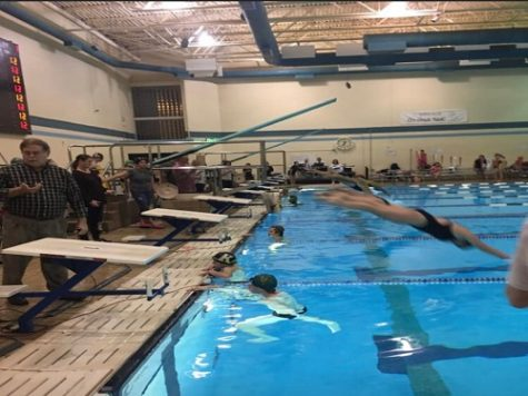 BOYS SWIM FINISHES the 50 meter freestyle and cheer the girls on from the water as they begin their next event.  Both the girls and boys teams defeated the Kellam Knights and the Kempsville Chiefs  as they look to continue their winning streak.