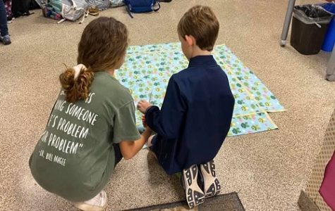 SENIOR AINSLEY ISENHOUR shows her middle school partner how to make a quilt. The quilts will go to those in need sometime in March.