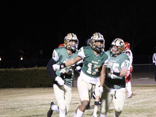 SENIOR DOMINIC WILSON, (left) celebrates a touchdown against the Marlins of Bayside High School, ultimately winning the game 34-16. Wilson was flanked by two teammates after his run into the end zone.