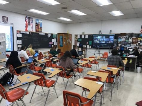 FIRST BLOCK JOURNALISM students socially distance during class, while virtual students are live on screen. Students are becoming more  adjusted to the new rules and regulations that have been put in place as safety precautions.