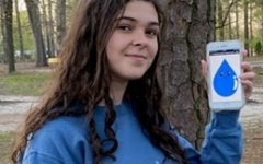 ENVIRONMENTAL CLUB MEMBER senior Cindy Eddington pledges to sustain the environment by accepting the practices of Wally the Water Drop. Eddington holds a photo of her drop as a means of raising awareness for environmental conservation.