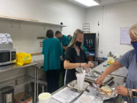 MRS. MEEKINGS ASSISTS students as they make food for this weeks Coffee Shop deliveries. The students are prepping for their usual Friday morning rush.